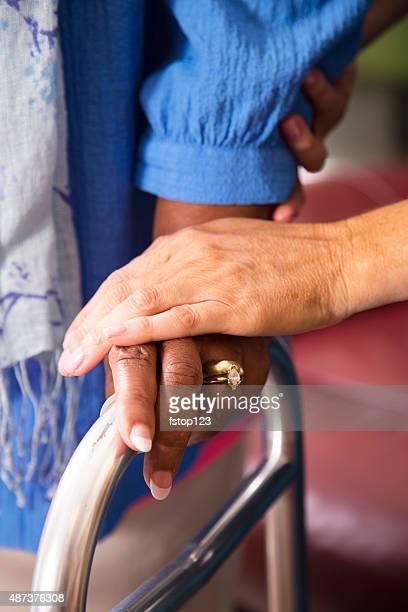 Casa healthcare enfermeira ajuda a mulher idosa utilização walker.