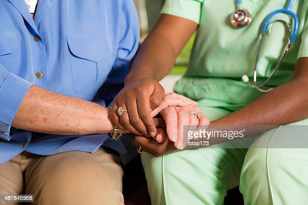 Maison healthcare Infirmière accueillir Femme âgée de mains.  Consoling. générosité.