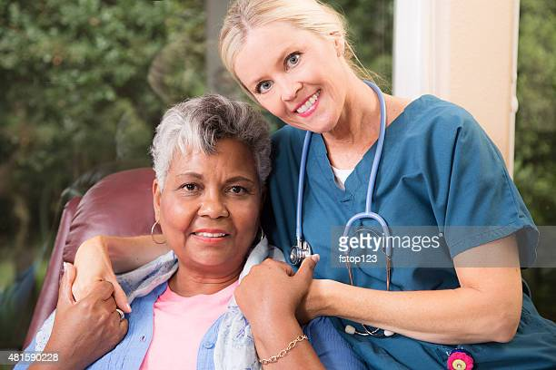 Home healthcare nurse with senior adult patient. Hug.