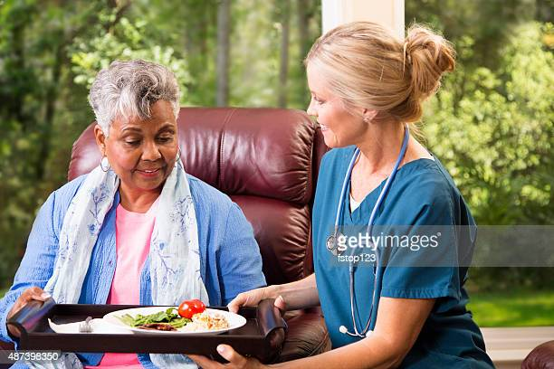 Home healthcare nurse with senior adult patient. Meal.