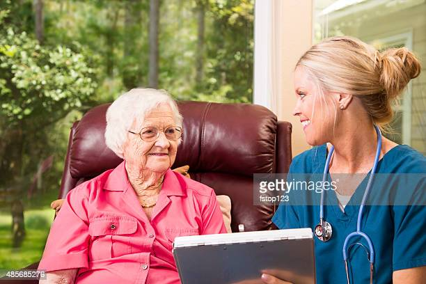 Home healthcare nurse with senior adult patient. Medical chart. Consultation.