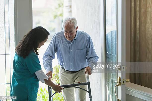 Startseite Gesundheitswesen Arbeiter hilft ältere Mann mit Walker