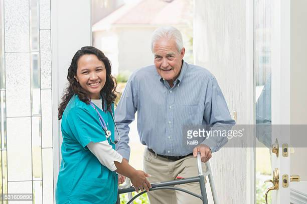 Home healthcare worker helping elderly man with walker