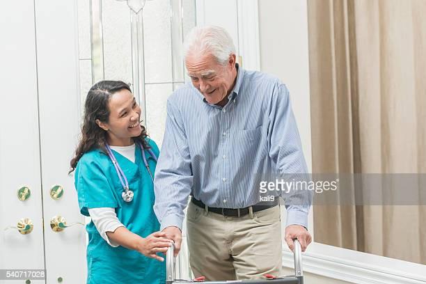 Casa personale sanitario aiutando uomo anziano con deambulatore