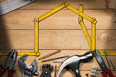 Home improvement concept - Yellow wooden ruler in the shape of a house on a wooden work table with work tools