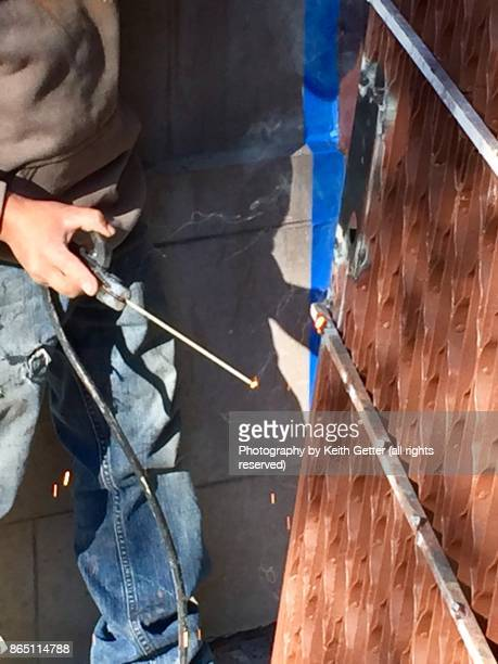 Home Improvements: An unrecognizable person using a welding tool to fix a metal gate door to a ground floor apartment