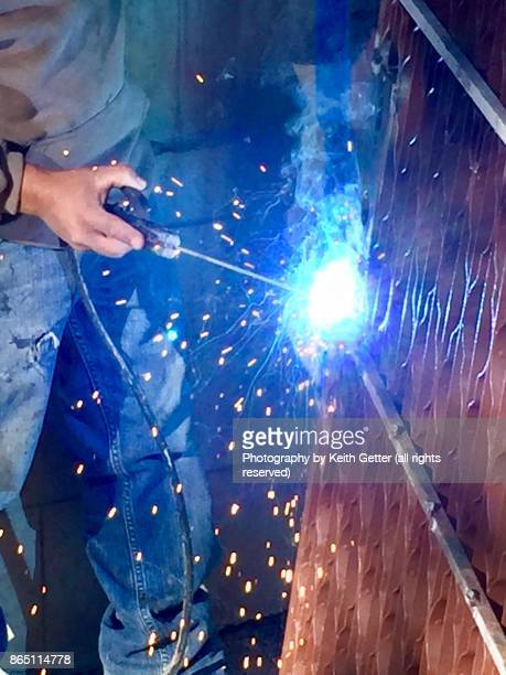 Home Improvements: Sparks fly as an unrecognizable person welds a metal gate door to a ground floor apartment