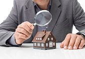 Inspector examining a house using a magnifying glass, house inspection and real estate concept