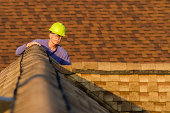 An inspector looks over a residential roof at the peak.