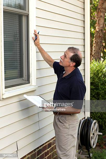 Home inspector examining the window outside of a white house