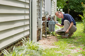 An inspector examines a residential gas meter and associated piping.