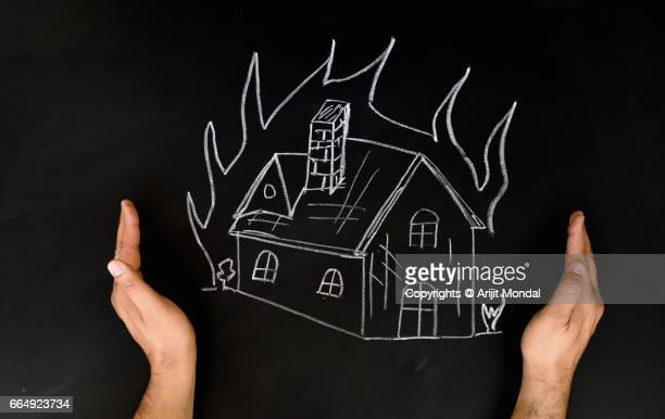 Home Insurance Concept Man Protecting House By Hands From Fire, Drawn on Blackboard