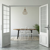 Open doors showing modern hipster vintage interior with dining table and chairs. pendant above. green plant, and cement floor with vintage rug. daylight scene template.