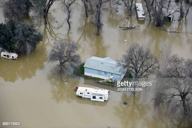 A home is seen marooned as the surrounding property is submerged in flood water in Oroville California on February 13 2017 Almost 200000 people were...
