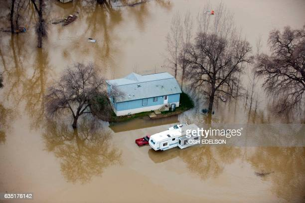 TOPSHOT A home is seen marooned as the surrounding property is submerged in flood water in Oroville California on February 13 2017 Almost 200000...