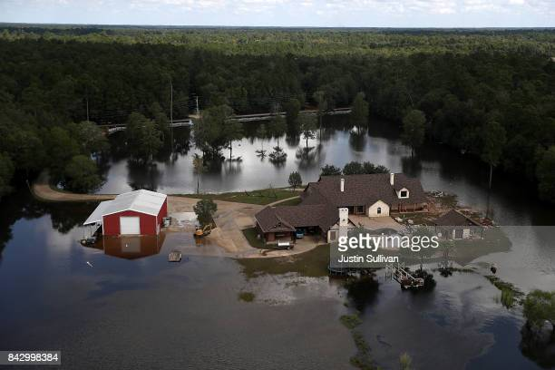 A home is surrounded by floodwaters on September 5 2017 near Beaumont Texas The Army National Guard is using helicopters to drop hay for cattle that...