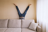Adult man hand standing behind sofa in the room. Home leisure activity spring cleaning dust allergy concept