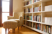 Home library with arm chair. Clean and modern decoration. Natural light coming from window.