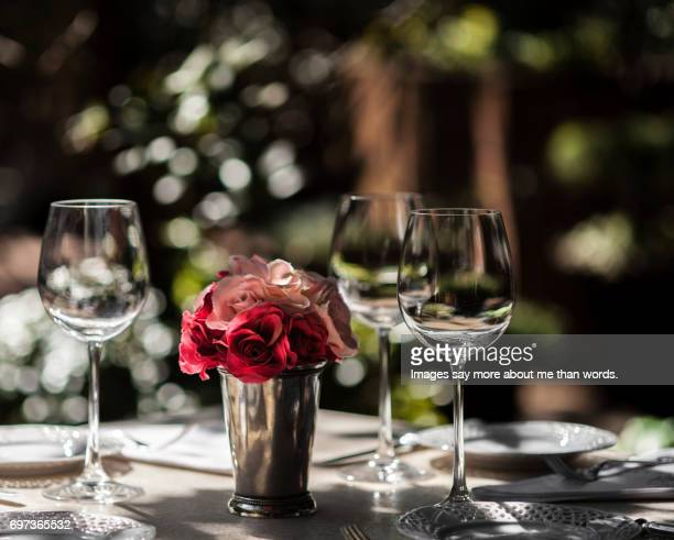 Home Moments - Table set outdoors with glasses, china and rose vase.