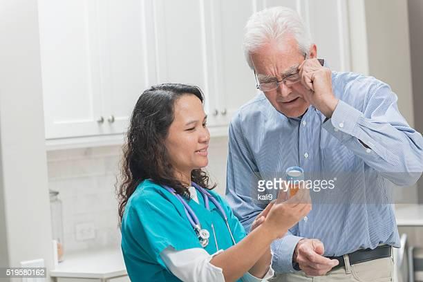Home nurse helping senior man with medication