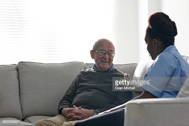 Home nurse taking care of senior man at home