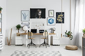 Modern home office interior with double desk, posters and accessories