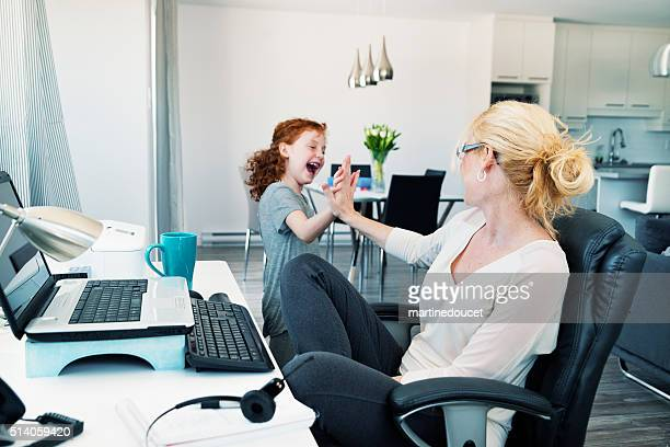 Home office, single mother conciliating work and family.