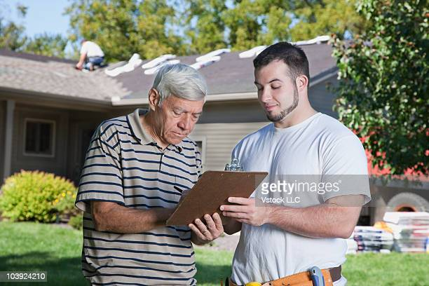 Home owner signing bill from construction worker
