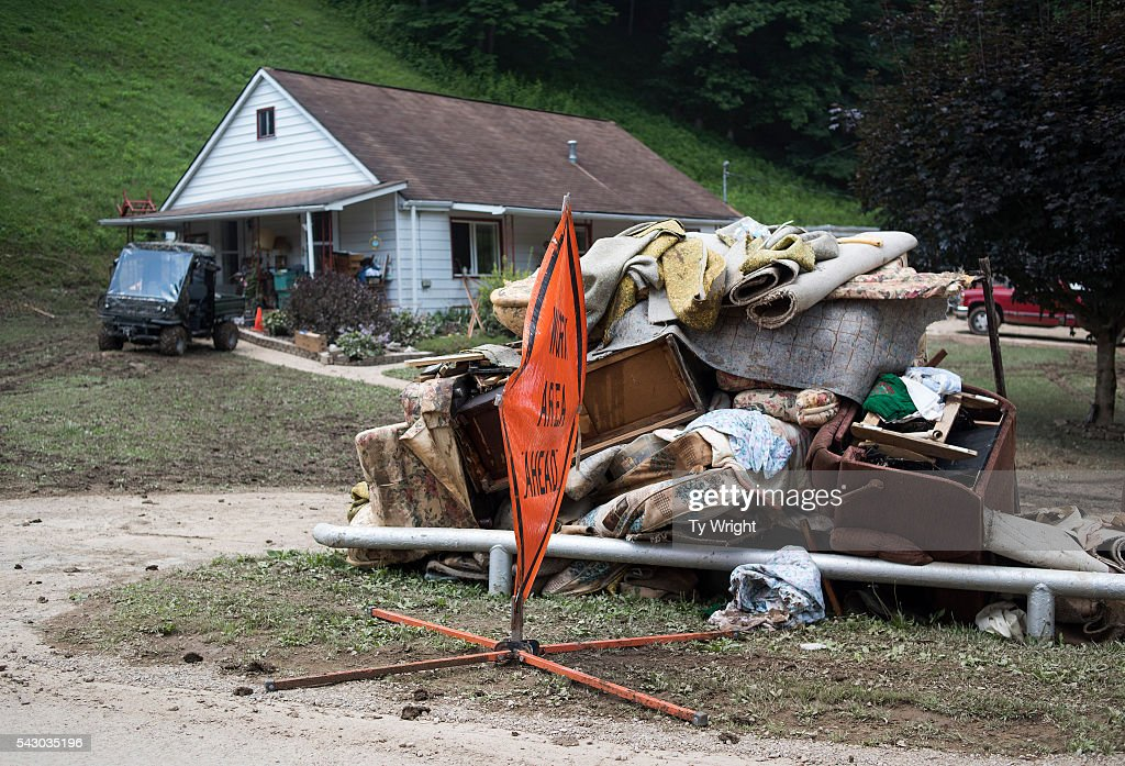 Home owners stack piles of water logged personal belongings along the side of State Route 119 on June 25, 2016 in Falling Rock, West Virginia. The flooding of the Elk River claimed the lives of at least 23 people in West Virginia.