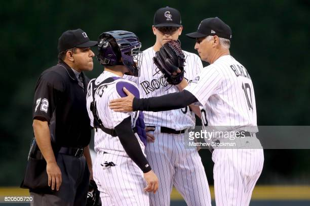 Home plate umpire Alfonso Marquez breaks up a conversation on the mound between starting pitcher Jeff Hoffman catcher Tony Wolters and manager Bud...