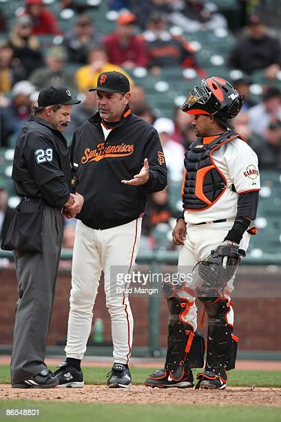 Home plate umpire Bill Hohn has a discussion with manager Bruce Bochy and catcher Bengie Molina of the San Francisco Giants during the game against...