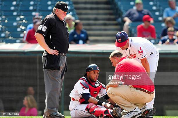 Home plate umpire Bill Miller watches as catcher Carlos Santana gets assistance from a trainer and manager Manny Acta of the Cleveland Indians after...
