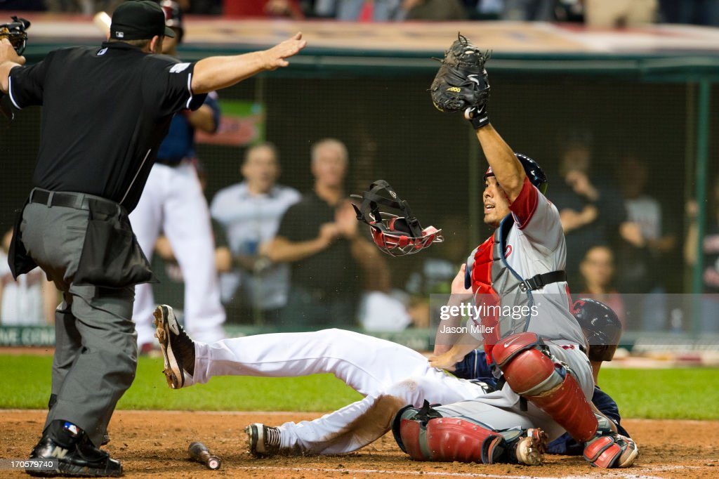 Home plate umpire Brian Knight #91 signals safe after <a gi-track='captionPersonalityLinkClicked' href=/galleries/search?phrase=Drew+Stubbs+-+Baseball+Player&family=editorial&specificpeople=4498334 ng-click='$event.stopPropagation()'>Drew Stubbs</a> #11 of the Cleveland Indians slid into catcher <a gi-track='captionPersonalityLinkClicked' href=/galleries/search?phrase=Kurt+Suzuki&family=editorial&specificpeople=682702 ng-click='$event.stopPropagation()'>Kurt Suzuki</a> #24 of the Washington Nationals to score the game-winning run in the ninth inning at Progressive Field on June 14, 2013 in Cleveland, Ohio. The Indians defeated the Nationals 2-1.