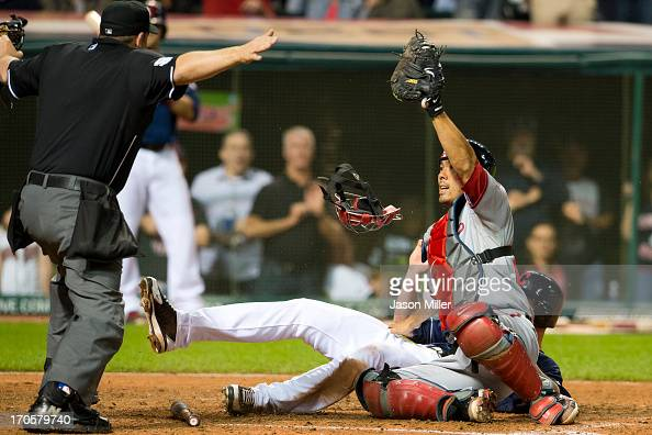Home plate umpire Brian Knight signals safe after Drew Stubbs of the Cleveland Indians slid into catcher Kurt Suzuki of the Washington Nationals to...