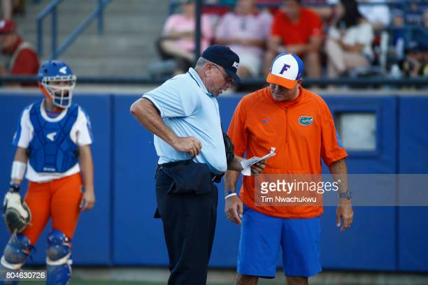 Home plate umpire Bryan Smith and Florida head coach Tim Walton confer during the Division I Women's Softball Championship held at ASA Hall of Fame...