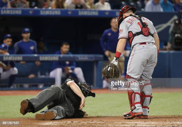 Home plate umpire Carlos Torres falls after being hit by a foul tip as Tucker Barnhart of the Cincinnati Reds watches in the fourth inning during MLB...