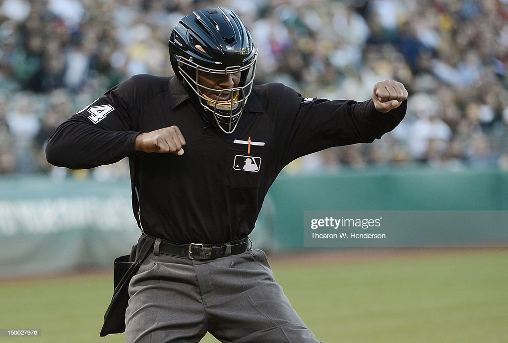 Home Plate umpire CB Bucknor calls strike three on a batter during an MLB baseball game between the Los Angeles Angels of Anaheim and the Oakland...