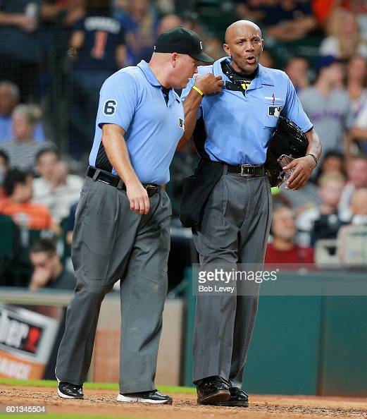 Home plate umpire CB Bucknor right talks with umpire Mark Carlson after he took a ball off his chest protector at Minute Maid Park on September 9...