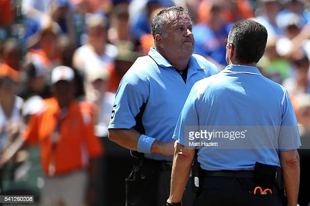 Home plate umpire Dale Scott is examined by head athletic trainer Richard Bancells of the Baltimore Orioles in the second inning during a game...