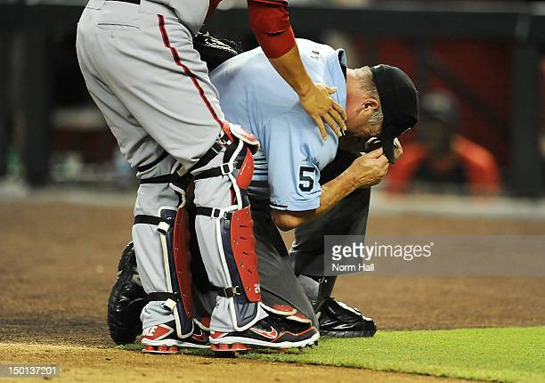 Home Plate Umpire Dale Scott takes a knee after taking a foul ball in the mask during a game between the Arizona Diamondbacks and the Washington...