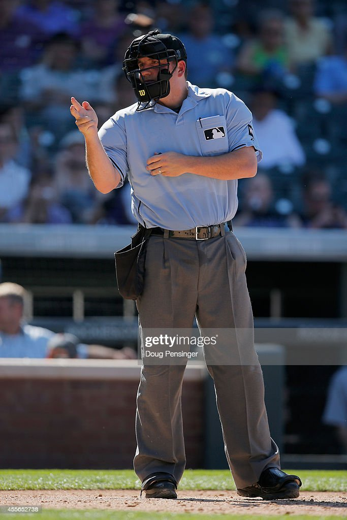 Home plate umpire Dan Bellino calls a strike as the Los Angeles Dodgers face the Colorado Rockies at Coors Field on September 17 2014 in Denver...