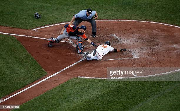 Home plate umpire Dan Bellino looks on as Jimmy Paredes of the Baltimore Orioles safely steals home plate under the tag of catcher Jason Castro of...
