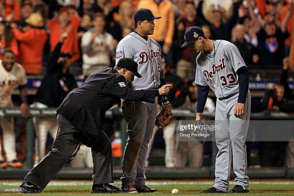 Home plate umpire Dan Iassogna (L) signals fair ball as Miguel Cabrera #24 and Drew Smyly #33 of the Detroit Tigers look on on a ball bunted by Gregor Blanco #7 of the San Francisco Giants in the seventh inning during Game Two of the Major League Baseball World Series at AT&T Park on October 25, 2012 in San Francisco, California.