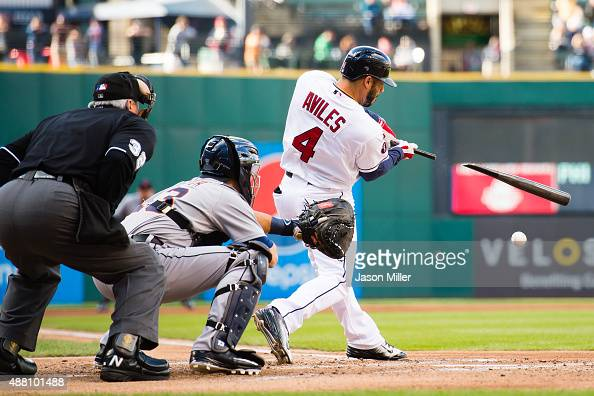 Home plate umpire Dana DeMuth and catcher Alex Avila of the Detroit Tigers watch as Mike Aviles of the Cleveland Indians hits a single during the...
