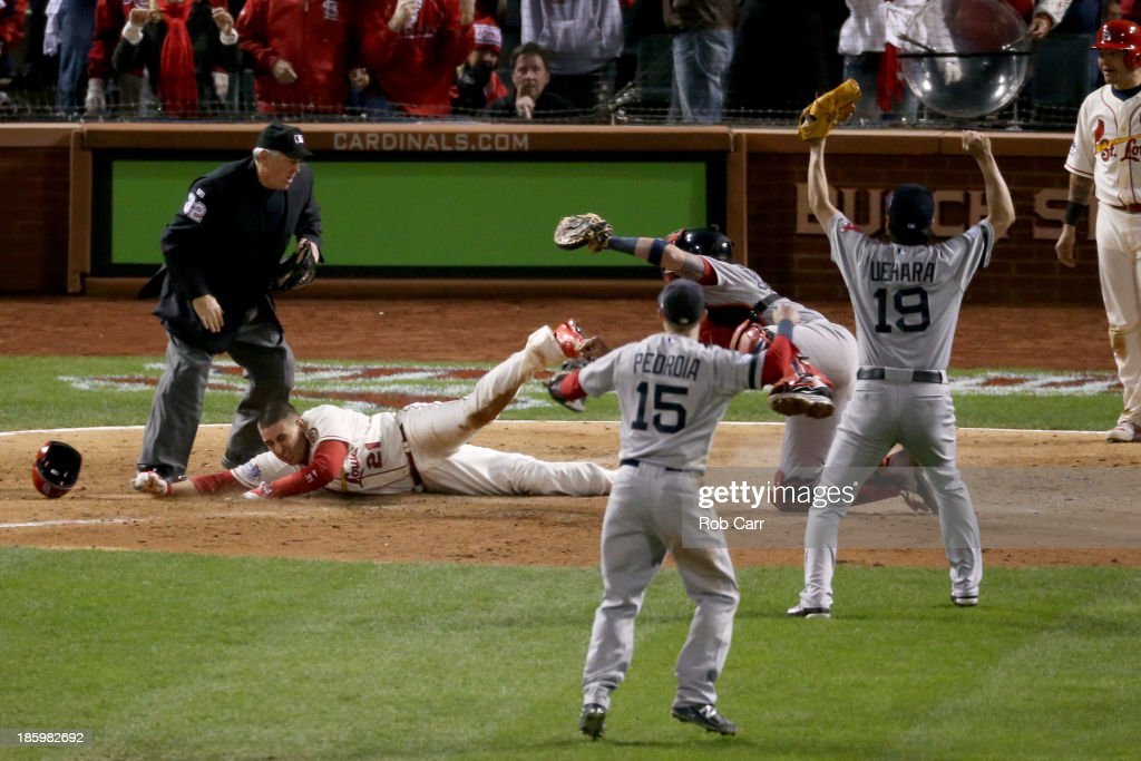 Home plate umpire Dana DeMuth calls Allen Craig of the St Louis Cardinals safe at home against Jarrod Saltalamacchia of the Boston Red Sox as Dustin...