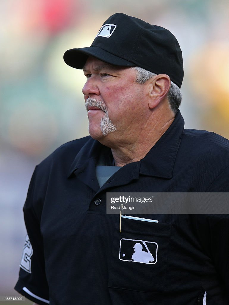 Home plate umpire Dana DeMuth works game two of a doubleheader between the Seattle Mariners and Oakland Athletics at O.co Coliseum on Wednesday, May 7, 2014 in Oakland, California.