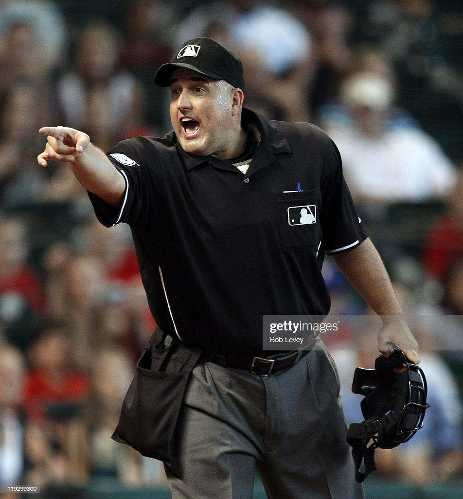 Home plate umpire Eric Cooper warns the Houston Astos dugout in the third inning about complaining about the strike zone during a baseball game...