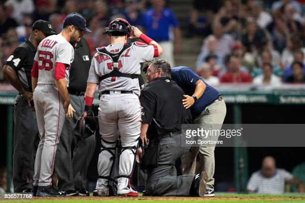 Home plate umpire Hunter Wendelstedt is examined by a member of the Cleveland Indians medical staff after being hit in the head with a warmup pitch...