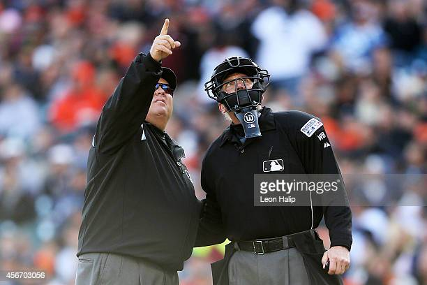Home plate umpire Jeff Kellogg looks up at a drone flying overhead during Game Three of the American League Division Series between the Baltimore...