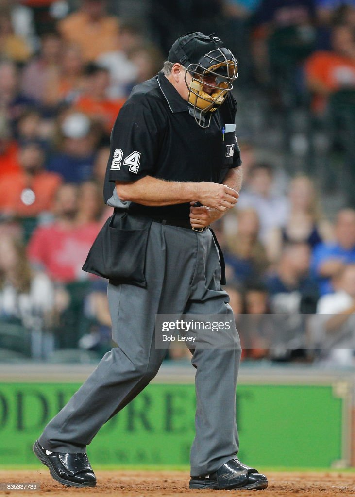 Home plate umpire Jerry Layne #24 holds his left wrist after being hit with a foul ball in the seventh inning at Minute Maid Park on August 18, 2017 in Houston, Texas.
